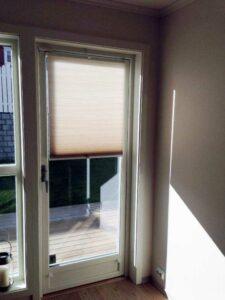 Lys plissegardin på verandadør.